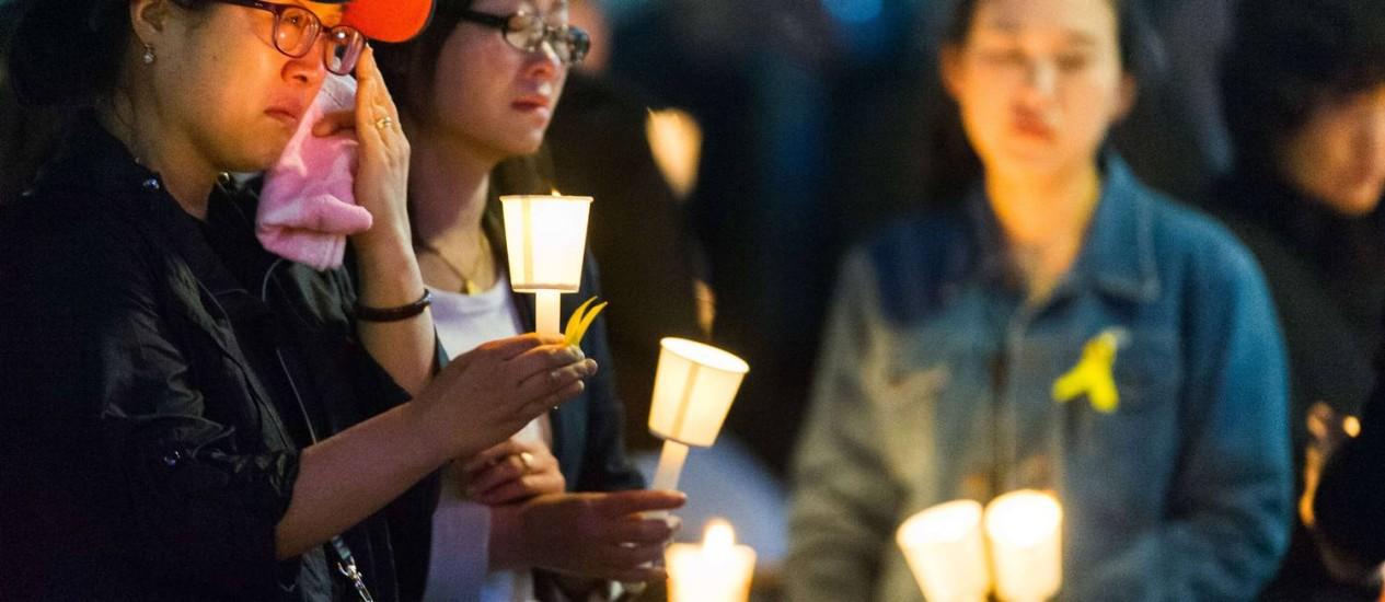 Luto. Em Ansan, sul-coreanos seguram velas em homenagem às vítimas do naufrágio. 183 corpos já foram encontrados, e 199 pessoas continuam desaparecidas Foto: KIM DOO-HO / AFP