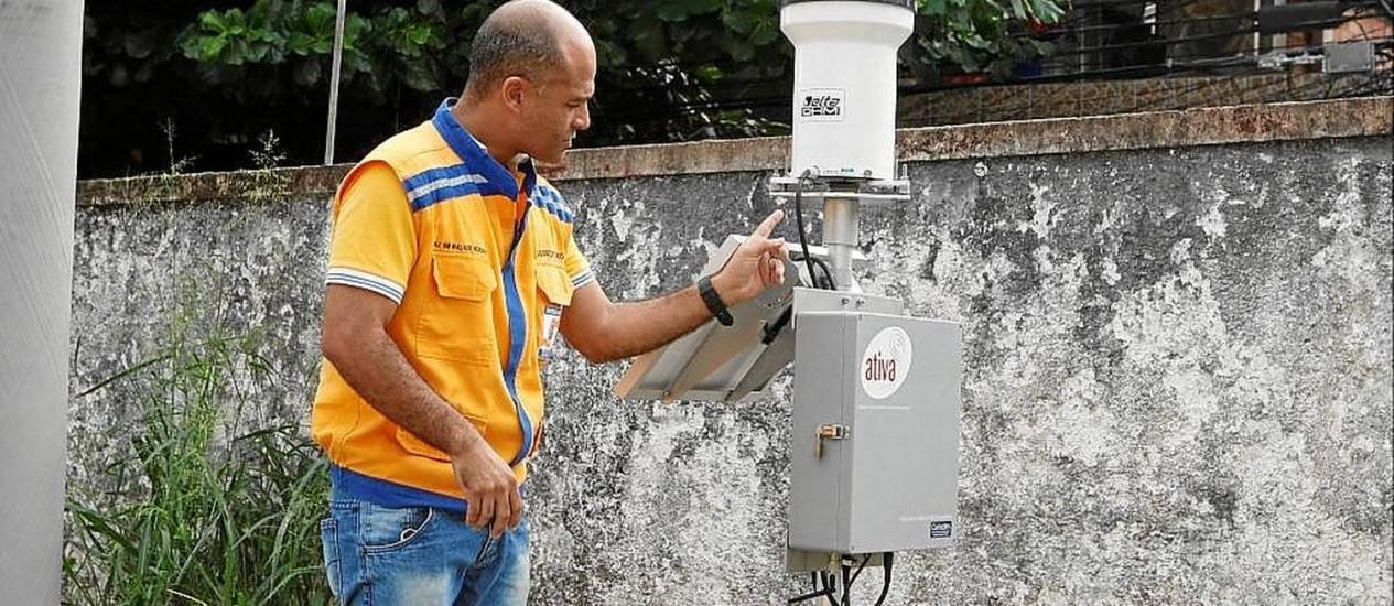 O subsecretário de Defesa Civil, major Walace, verifica os dados de um aparelho em Charitas Foto: Eduardo Naddar / Eduardo Naddar