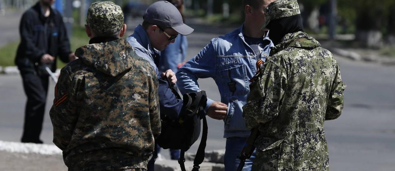 Dois separatistas checam documentos de dois homens no leste da Ucrânia, onde os membros da OSCE estão detidos Foto: MAX VETROV / AFP