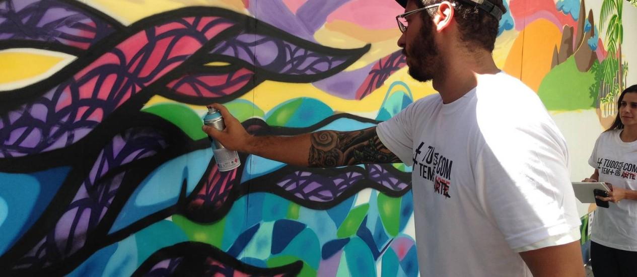 Artista em ação durante a grafitagem dos tapumes Foto: Divulgação
