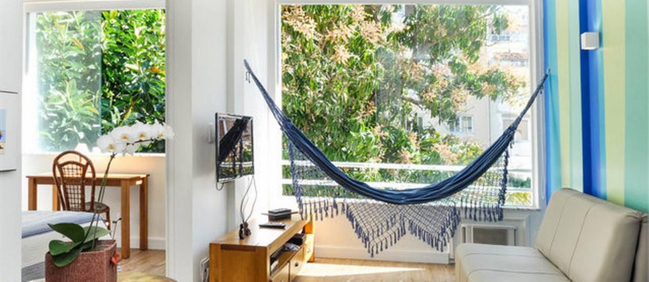 Apartamento alugado para temporada no Arpoador ganhou móveis simples, mas funcionais, como o sofá-cama da sala. Rede e paredes coloridas dão charme ao espaço reformado pela Odara Arquitetura Foto: Divulgação