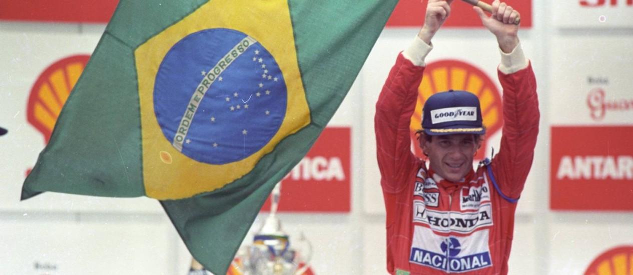 Determinação. Depois de vencer pela primeira vez o Grande Prêmio do Brasil, em 1991, guiando em condições extremas nas últimas voltas, Ayrton Senna ergue a bandeira nacional no pódio de Interlagos, para delírio da torcida brasileira Foto: Fernando Pereira / Fernando Pereira/24-03-1991