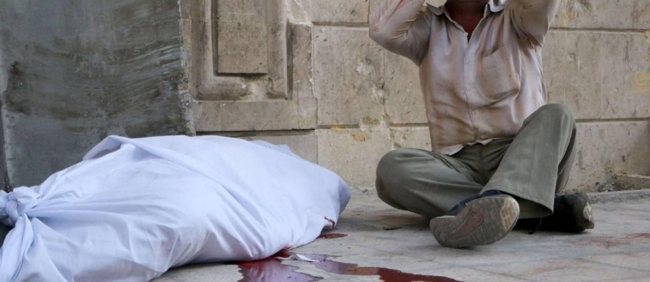 Homem chora ao lado de corpo durante os ataques em Aleppo, que deixaram 21 mortos neste domingo. Síria está próxima de se livrar de 100% do seu arsenal de armas químicas. Foto: Fadi al-Halabi / AFP