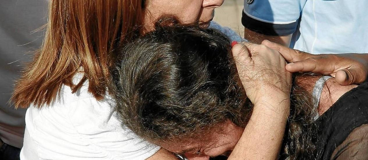 Morte após confissões. Karla (esquerda), uma das filhas de Malhães, e a viúva do militar, durante o enterro , sábado Foto: Antonio Scorza/26-4-2014