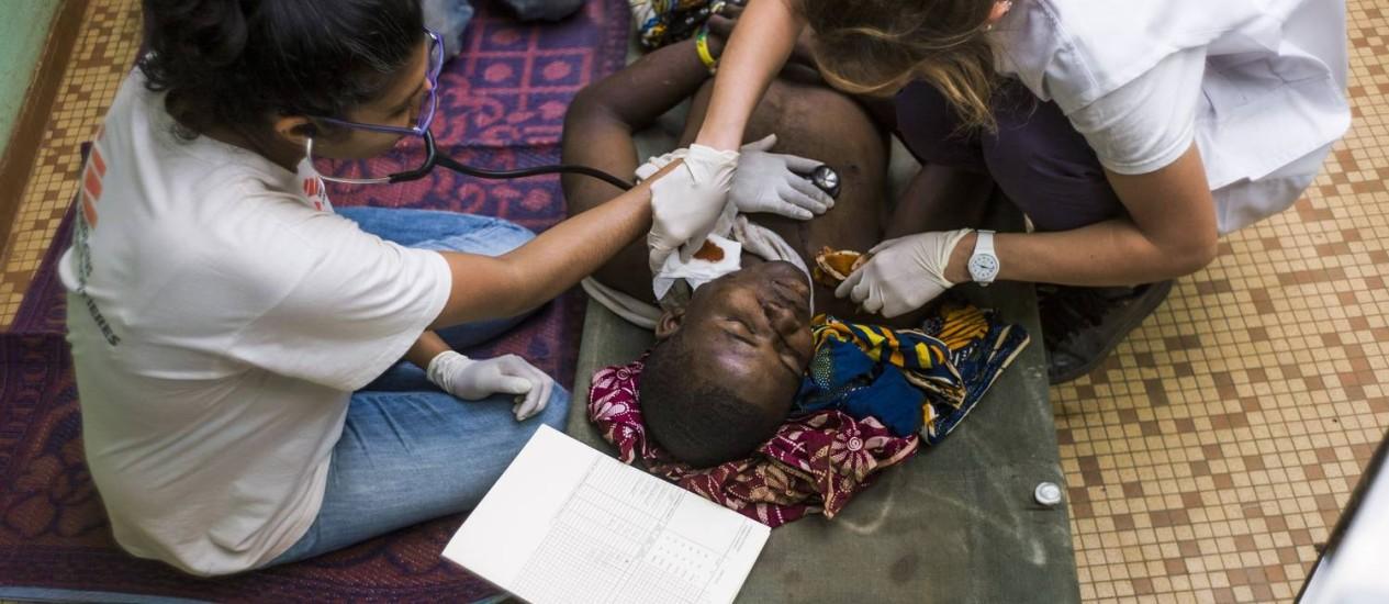 Foto de dezembro de 2013 mostra um homem ferido durante confrontos entre ex-rebeldes Seleka e milicianos anti-Balaka recebendo tratamento da equipe da Médicos Sem Fronteiras em Bangui Foto: FRED DUFOUR / AFP