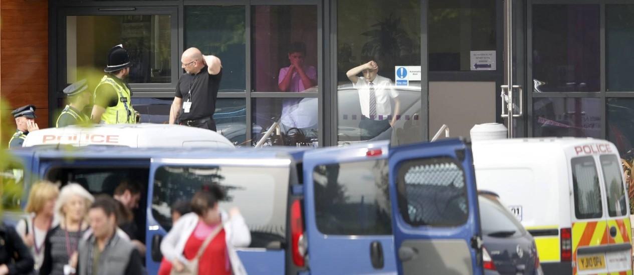 Carros policiais diante da Corpus Christi Catholic College, em Leeds: a professora Anne Maguire foi morta a facadas Foto: DARREN STAPLES / REUTERS
