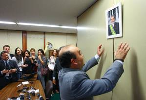 O deputado Bernardo Santana (PR/MG) coloca retrato do ex-presidente Lula na parede do escritório da liderança do partido durante entrevista coletiva Foto: André Coelho / Agência O Globo