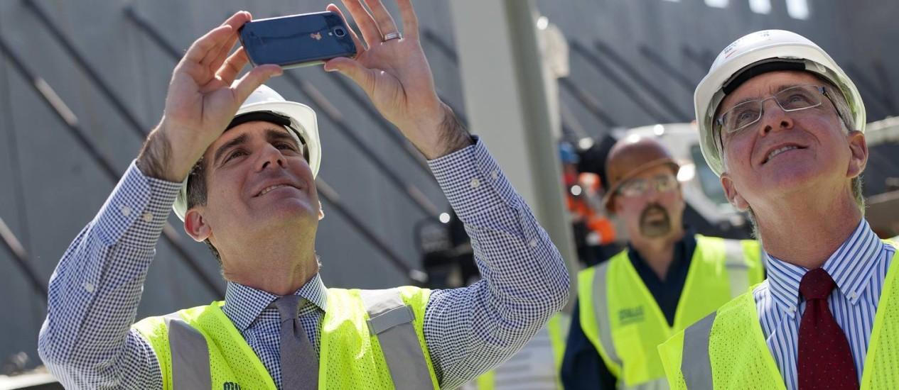 Eric Garcetti, prefeito de Los Angeles, tira fotos em uma construção na cidade Foto: MICHAL CZERWONKA/NYT