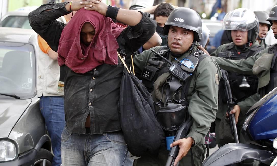 Manifestante é detido pela Guarda Nacional durante uma marcha antigoverno em Caracas Foto: CHRISTIAN VERON / REUTERS