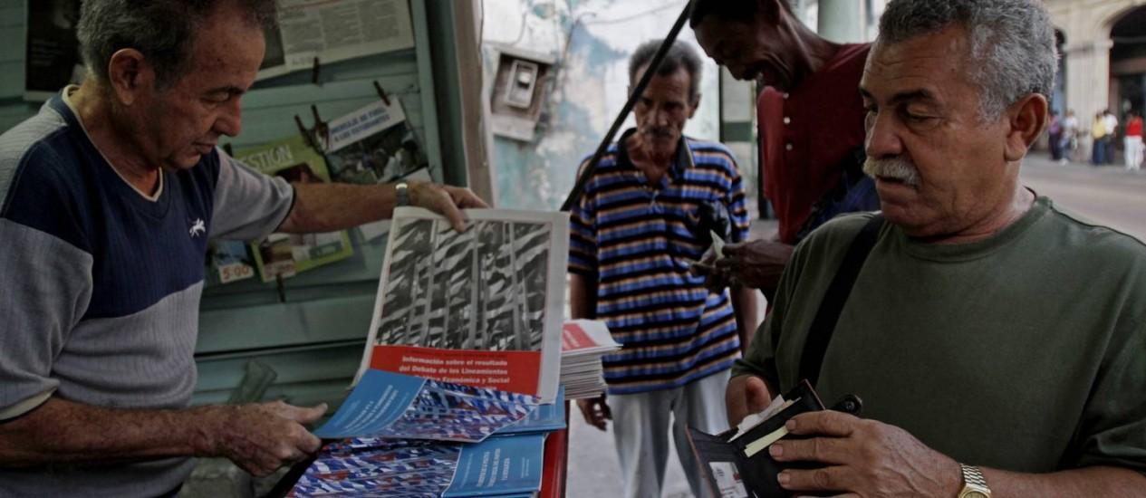 Um homem compra cópias de documentos que explicam as diretrizes e as mudanças econômicas aprovadas pelo Partido Comunista em 2011 Foto: Franklin Reyes / AP