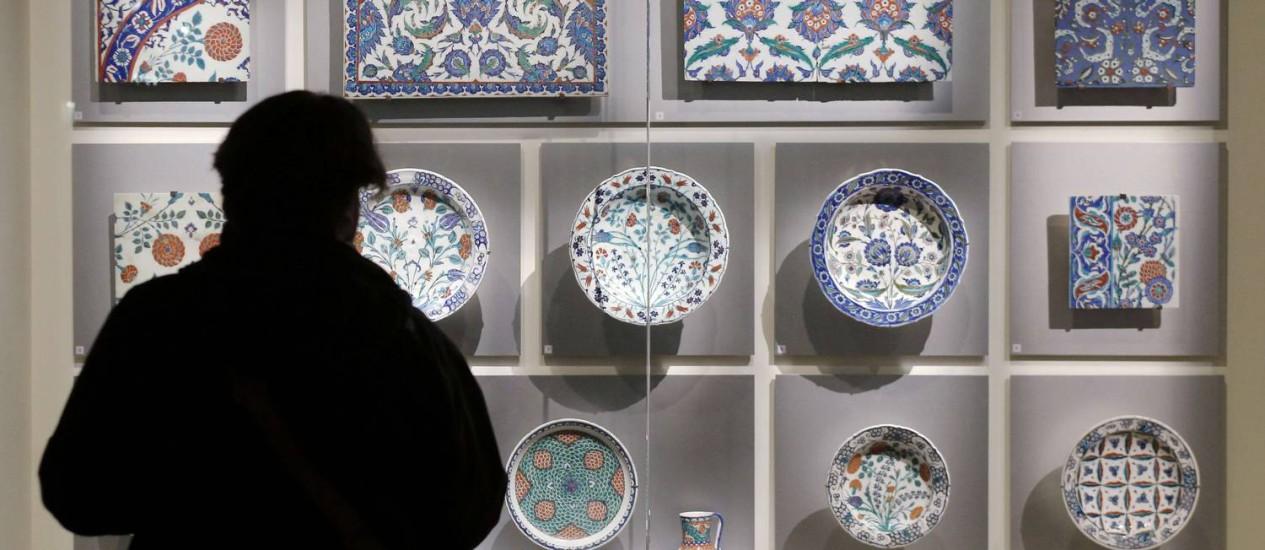 """Um visitante diante de amostras de cerâmica do Imério Otomano durante a exibição """"O nascimento de um museu"""", no Louvre, em Paris, a primeira exibição de parte da coleção permanente do Louvre de Abu Dhabi, que será inaugurado em 2015 (AFP/François Guillot) Foto: FRANCOIS GUILLOT / AFP"""