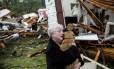 Mississippi. Constance Lambert abraça seu cão, resgatado de sua casa destruída por tornado em Tupelo