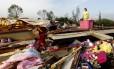 Teresa Ingram procura por seus pertences em meio a escombros após a passagem de um tornado em Athens, no Alabama