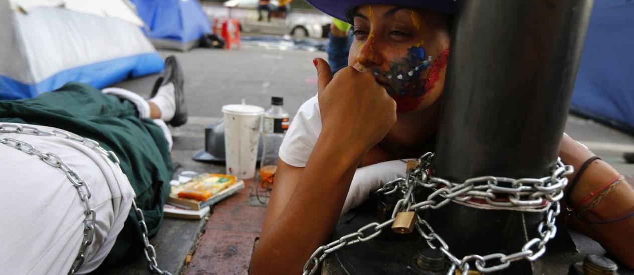 Manifestante antigoverno se amarra em poste durante protesto em frente a escritório da ONU em Caracas Foto: JORGE SILVA / REUTERS
