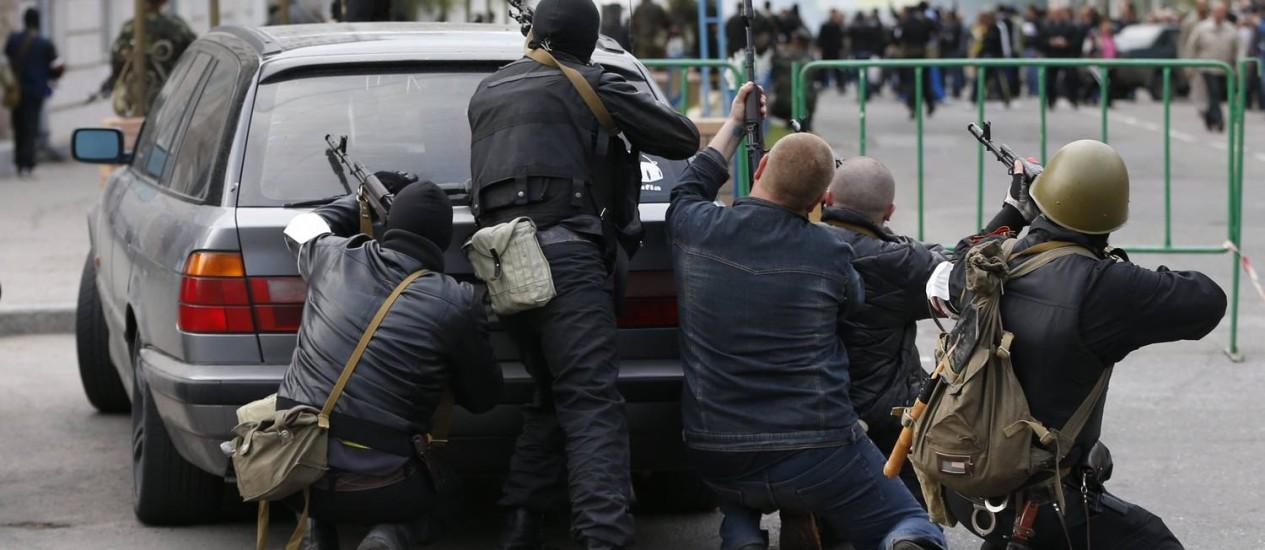Manifestantes pró-Rússia se protegem atrás de um carro em Luhansk. Grupo de 20 mascarados armados tomou prédios públicos nesta terça-feira Foto: VASILY FEDOSENKO / REUTERS