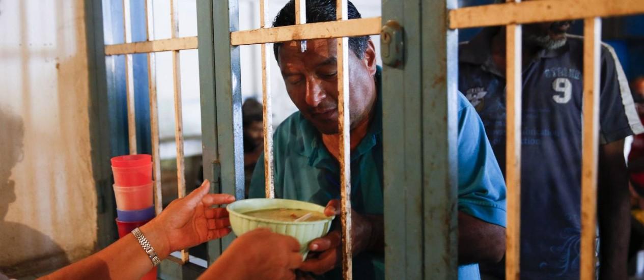Uma voluntária oferece um prato de sopa a um homem no refeitório Madre Teresa de Calcutá, em Caracas Foto: Carlos Garcia Rawlins / REUTERS
