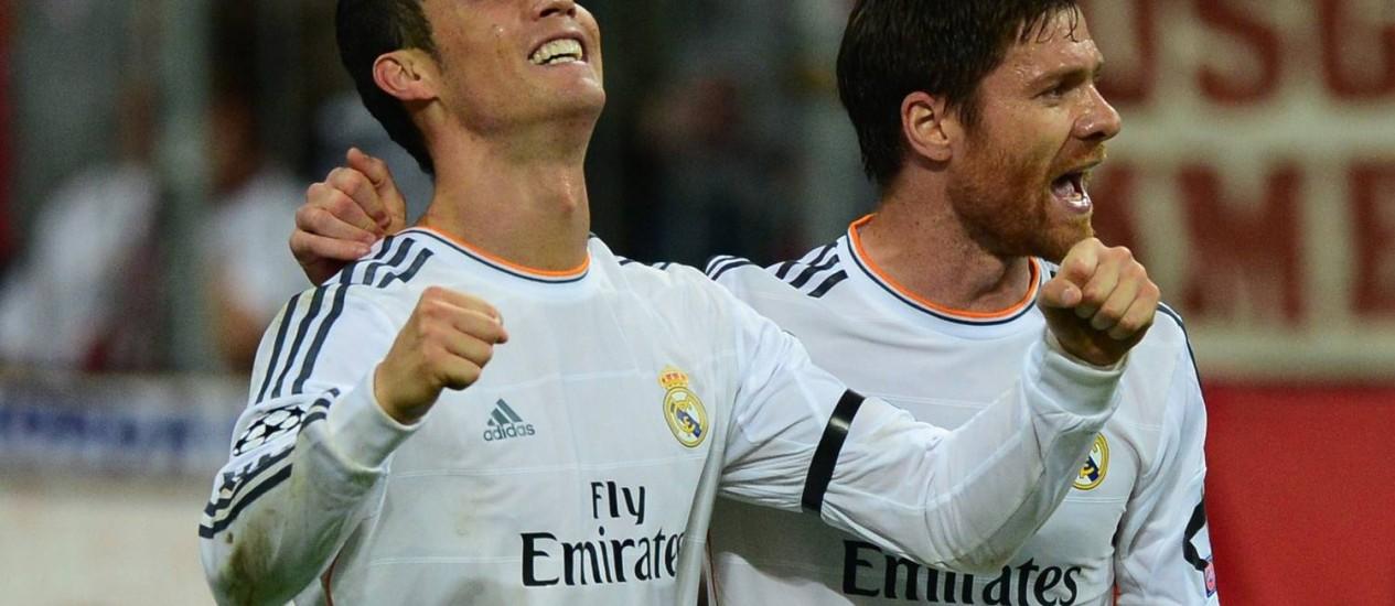 Cristiano Ronaldo comemora um dos gols nos 4 a 0 sobre o Bayern de Munique, ao lado de Xabi Alonso Foto: JOHN MACDOUGALL / AFP