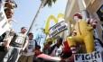 Trabalhadores protestam contra os baixos salários em frente a um McDonald's