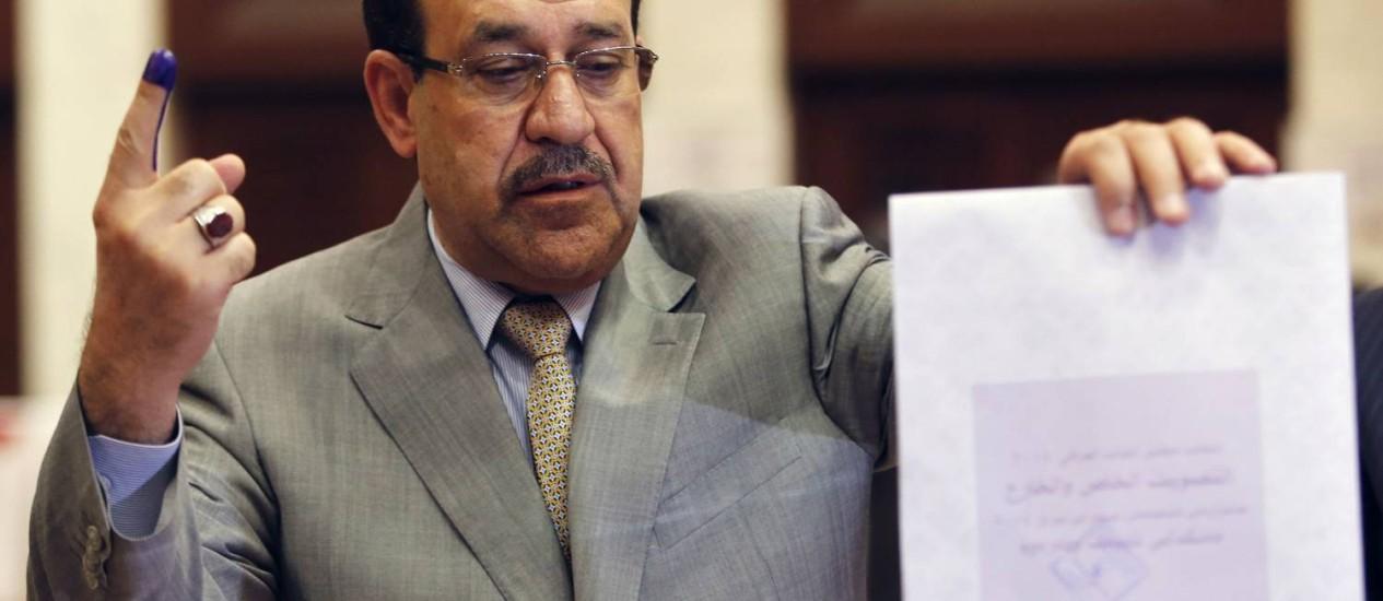 O primeiro-ministro do Iraque, Nouri al-Maliki, deposita a cédula de votação na urna Foto: AHMED JADALLAH / Reuters