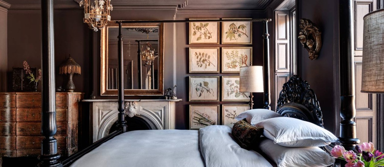 Ares de palacete no quarto do casal que ganhou paredes em tom berinjela e cama com armação para dossel. Gravuras de botânica do século XVII fazem parte da decoração do ambiente Foto: Bruce Buck/ New York Times