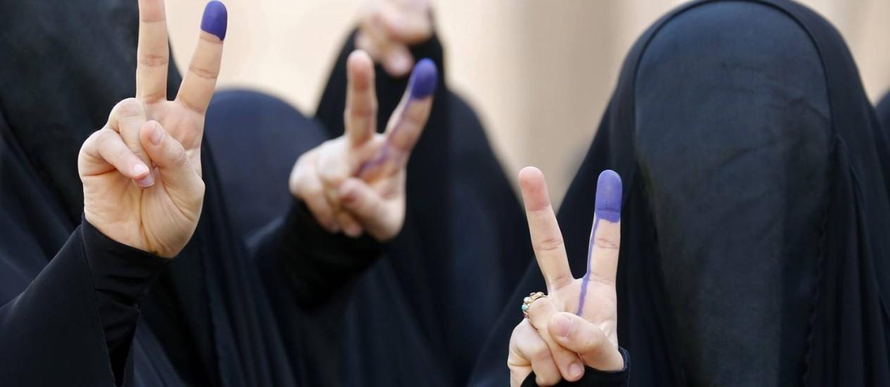 Mulheres iraquianas totalmente cobertas por burca fazem sinal de vitória com os dedos manchados de tinta depois de votarem nas eleições legislativas Foto: SABAH ARAR / AFP
