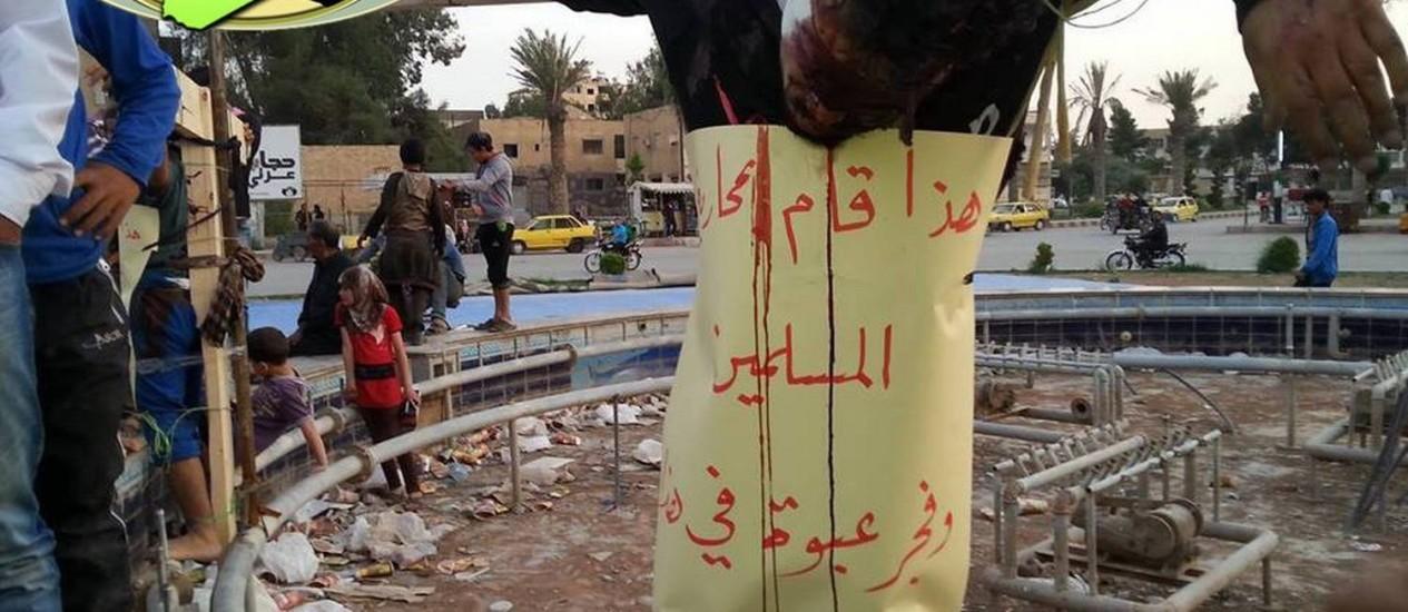 Um dos homens executados e crucificados em Raqqa, na Síria: cartaz afirma que ele combateu muçulmanos e explodiu uma granada Foto: HO - / Observatório Sírio de Direitos Humanos/AFP