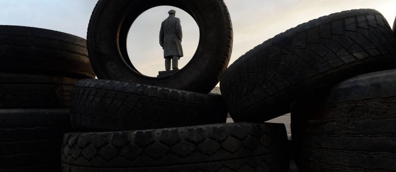 Estátua de Lênin vista através de pneus de barricadas em Slaviansk Foto: VASILY MAXIMOV / AFP