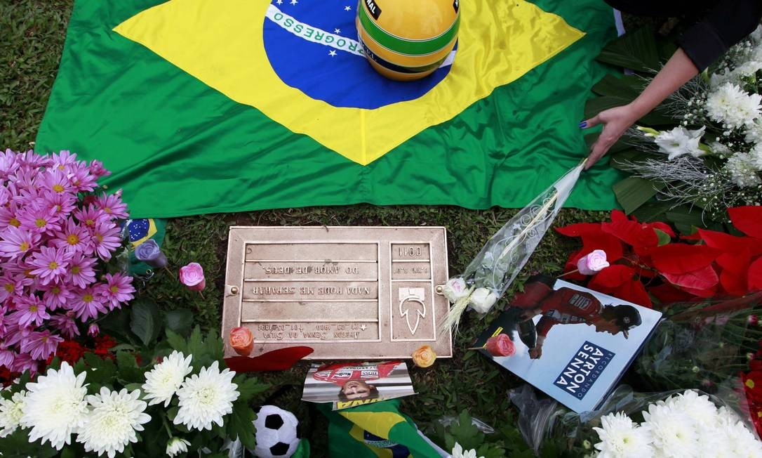 A woman deposits a flower at the tomb of Brazil's Formula One driver Ayrton Senna, on the 20th anniversary of his death, in Sao Paulo May 1, 2014. Senna had just moved to Williams and was in only his third race for that team when he crashed and died at the San Marino Grand Prix on May 1, 1994. REUTERS/Paulo Whitaker (BRAZIL - Tags: ANNIVERSARY SPORT MOTORSPORT F1 OBITUARY) PAULO WHITAKER / REUTERS