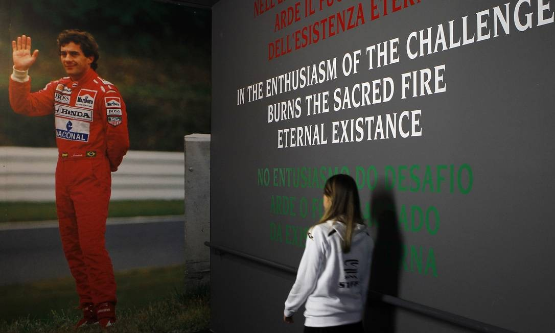 A girl walks near a picture of Brazilian Formula One driver Ayrton Senna during an exhibition at the Imola race track, northern Italy May 1, 2014. A tribute event was held at Imola race track in memory of Formula 1 drivers Senna and Roland Ratzenberger to mark the 20th anniversary of their deaths. REUTERS/Alessandro Garofalo (ITALY - Tags: ANNIVERSARY SPORT MOTORSPORT F1) ALESSANDRO GAROFALO / REUTERS