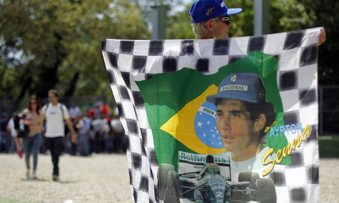 A woman holds a flag depicting Brazilian Formula One driver Ayrton Senna during a memorial at the Imola race track, northern Italy May 1, 2014. A tribute event was held at Imola race track in memory of Formula 1 drivers Ayrton Senna and Roland Ratzenberger to mark the 20th anniversary of their deaths. REUTERS/Alessandro Garofalo (ITALY - Tags: SPORT MOTORSPORT F1 OBITUARY) ALESSANDRO GAROFALO / REUTERS
