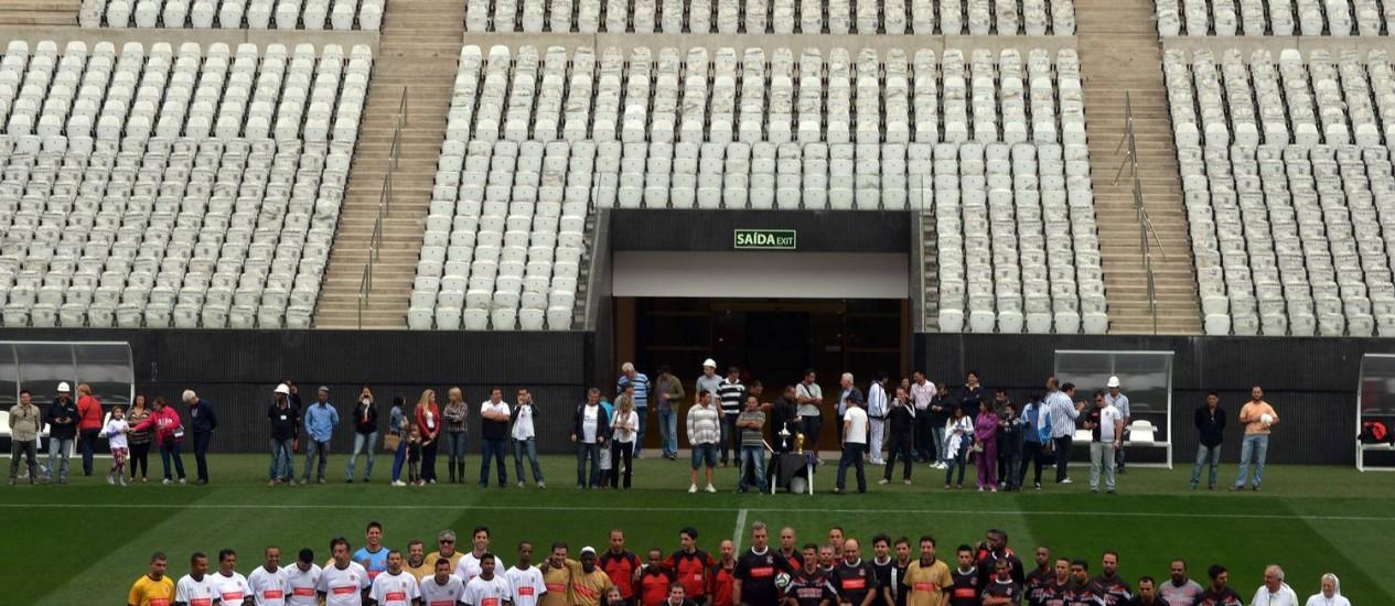 No Dia do Trabalhador. Funcionários posam antes da primeira partida do Itaquerão, que será o palco de abertura da Copa do Mundo, no dia 12 de junho Foto: NELSON ALMEIDA / AFP