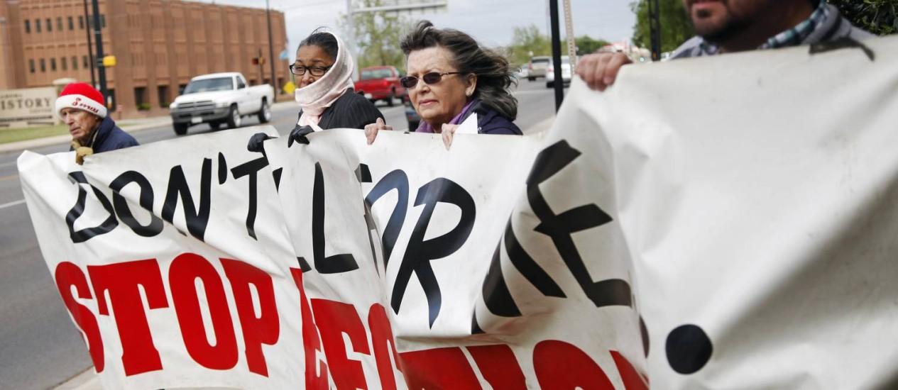 John Walters, Jana Lewis-Harkins, Fannie Bates e Aaron Baker (da esq. para a dir.) seguram um banner durante um protesto em frente à mansão do governador de Oklahoma contra a execução de detentos Foto: KT King / AP