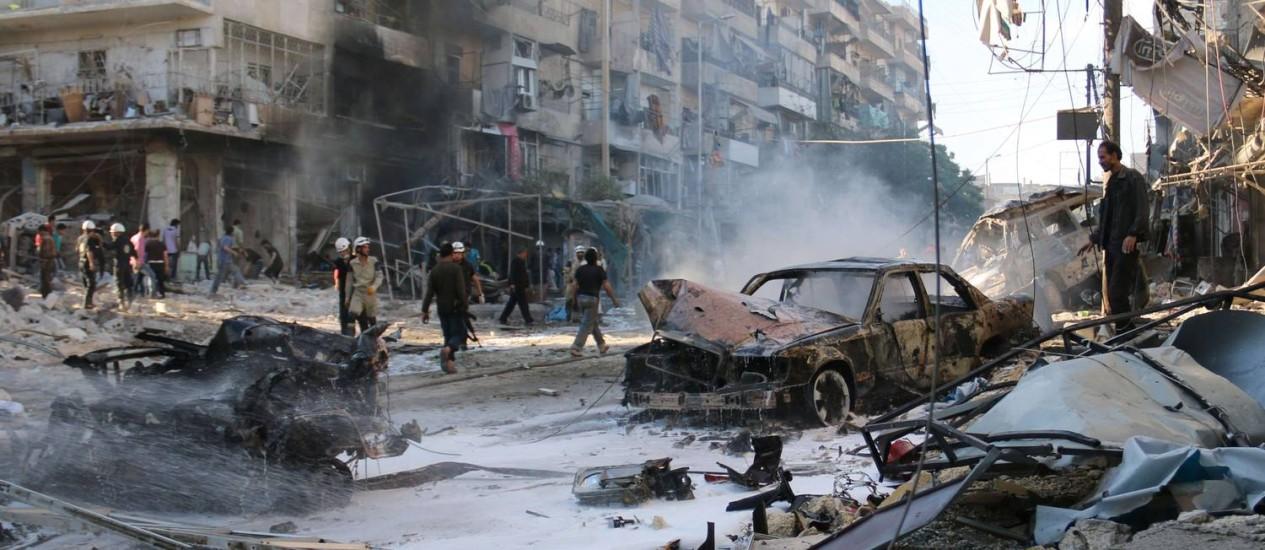 Sírios se reúnem no local de ataques aéreos que teriam sido perpetrados por forças do governo no bairro de Halak, em Aleppo Foto: ZEIN AL-RIFAI / AFP