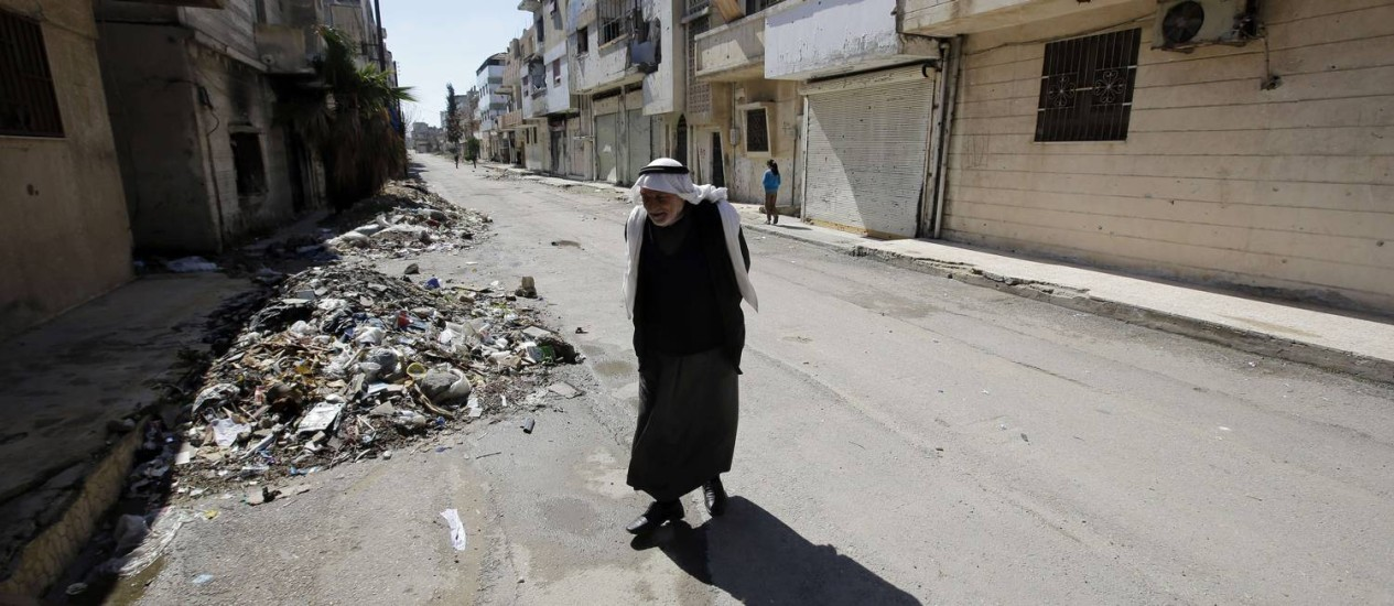Homem caminha pelo bairro de Baba Amr, retomado pelo governo sírio (15-03-2014) Foto: Joseph Eid / AFP