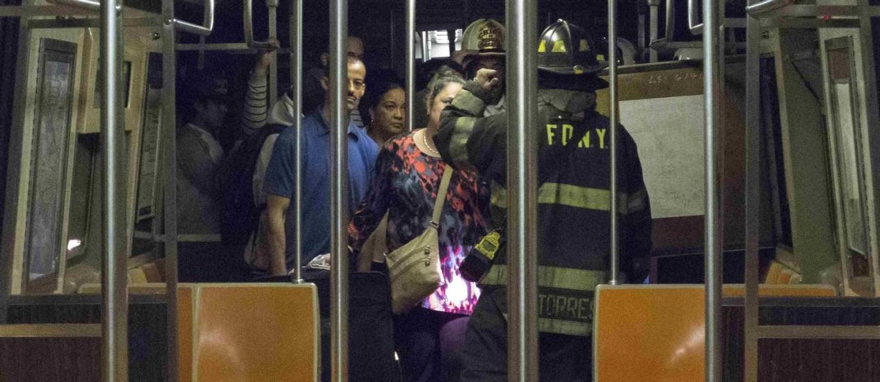 Bombeiro dá instruções para passageiros de metrô que descarrilou em Nova York Foto: REUTERS