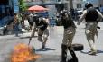 Policiais haitianos reprimem protesto contra o governo na capital, Porto Príncipe: Minustah diminui gradativamente tarefas de policiamento