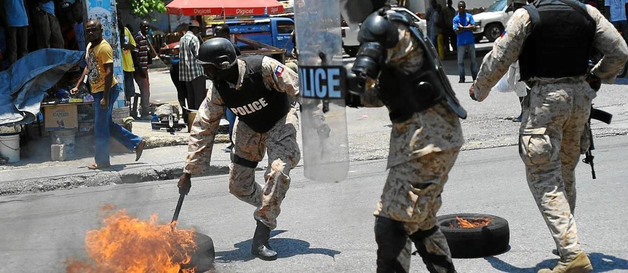Policiais haitianos reprimem protesto contra o governo na capital, Porto Príncipe: Minustah diminui gradativamente tarefas de policiamento Foto: 1-5-2004 / AFP