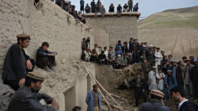 Afegãos olham a busca desesperada das equipes de resgate por sobreviventes no distrito de Argo, na província de Badakhshan Foto: SHAH MARAI / AFP