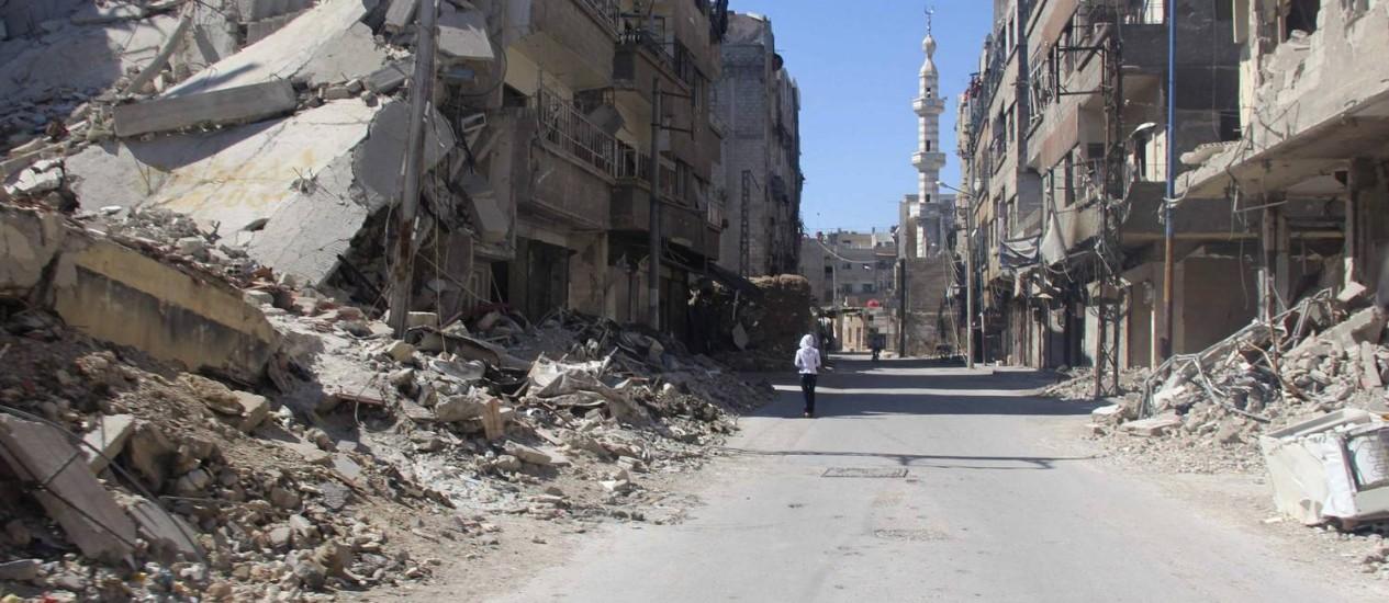 Um morador caminha por edifícios destruídos em Zamalka, no subúrbio de Damasco Foto: STRINGER / REUTERS
