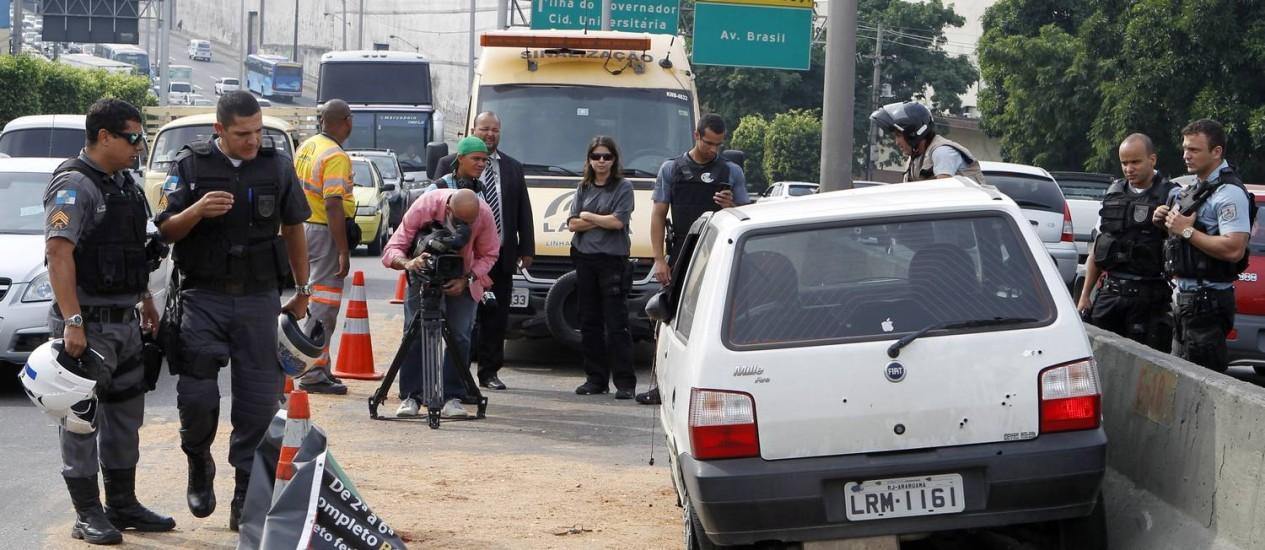Policiais observam o veículo do PM morto a tiros na Linha Amarela Foto: Gustavo Miranda / Agência O Globo