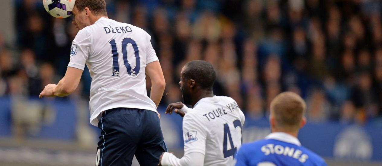 Dzeko cabeceia para marcar o terceiro gol do City Foto: Paul Ellis / AFP