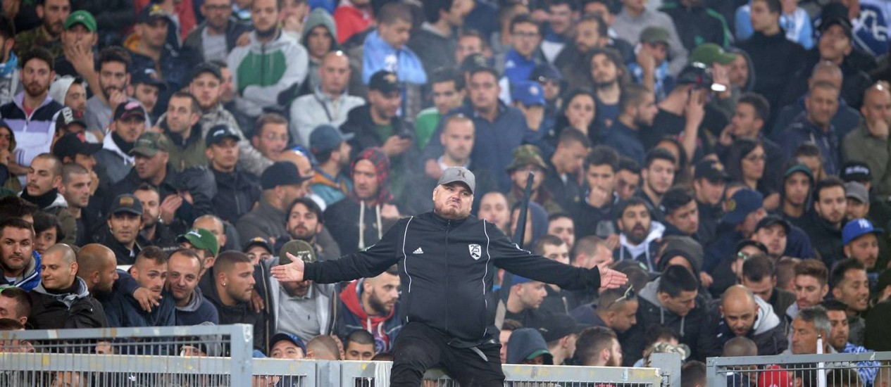 Um torcedor do Napoli no alto da grade antes da partida entre Fiorentina e Napoli pela final da Copa da Itália Foto: Filippo Monteforte / AFP