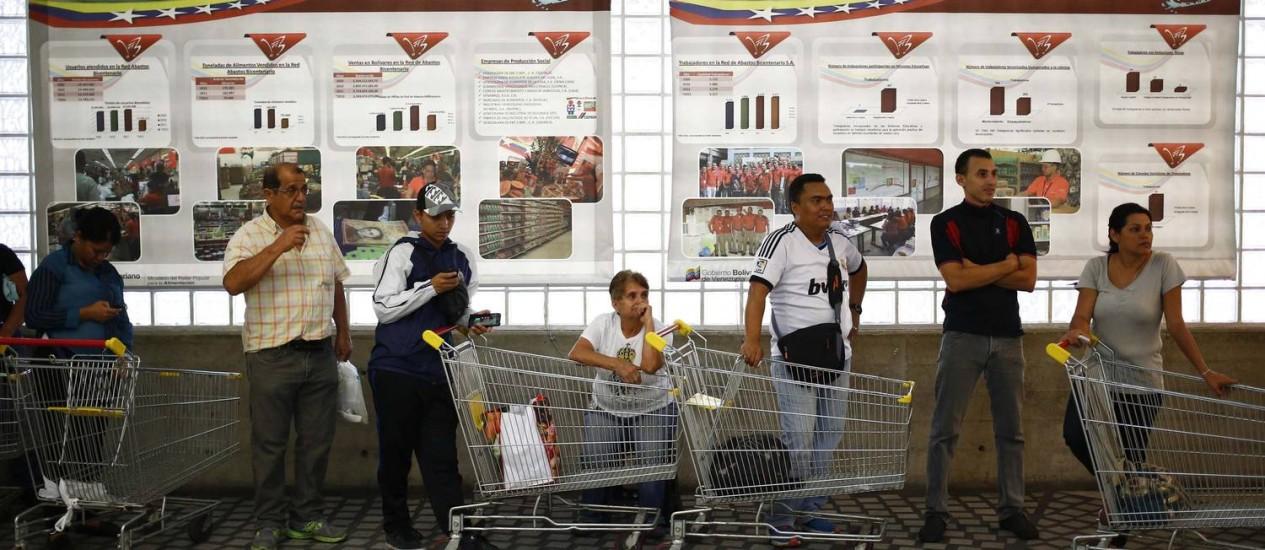 Paciência. Clientes fazem fila em supermercado de Caracas: crise cambial já afeta indústria local de alimentos Foto: JORGE SILVA / REUTERS