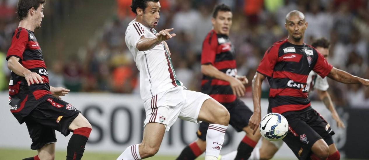 Fred tenta o chute, cercado por três rubro-negros Foto: Guito Moreto / Agência O Globo
