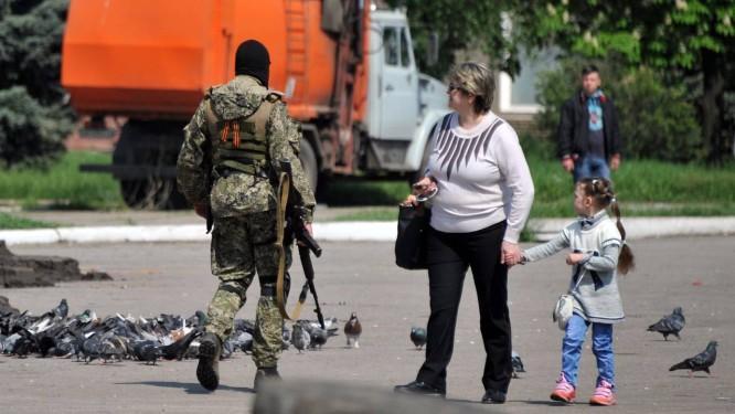 Mulher caminha com filha ao lado de militante pró-Rússia com uma metralhadora no centro da cidade ucraniana de Kramatorsk Foto: GENYA SAVILOV / AFP