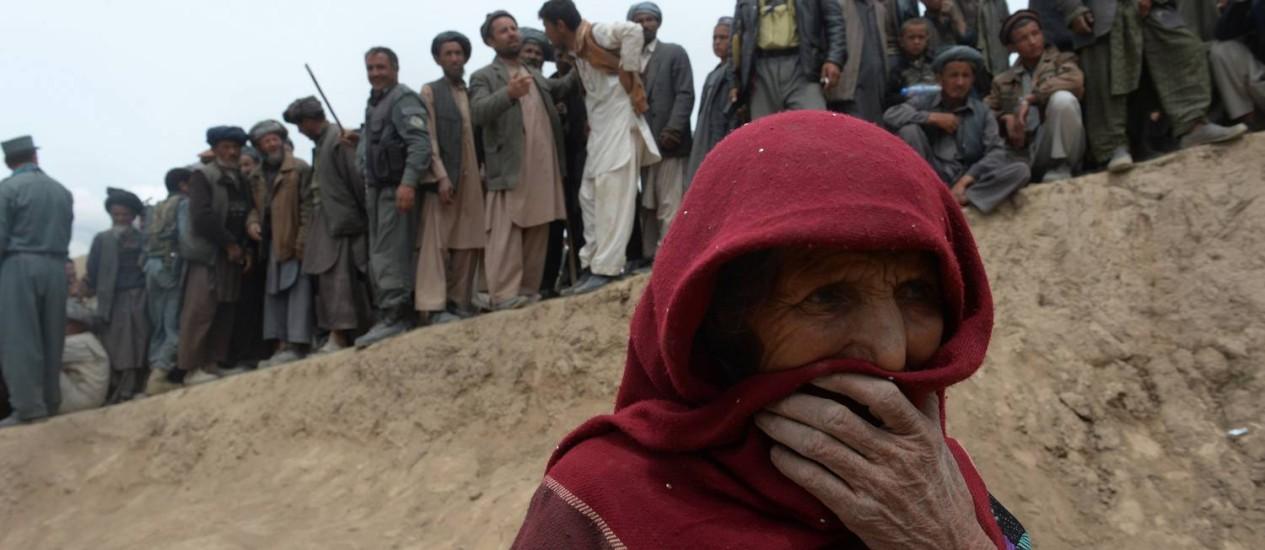 Moradores fazem fila para pegar suprimentos de emergência no local do desastre no distrito de Argo Foto: SHAH MARAI / AFP