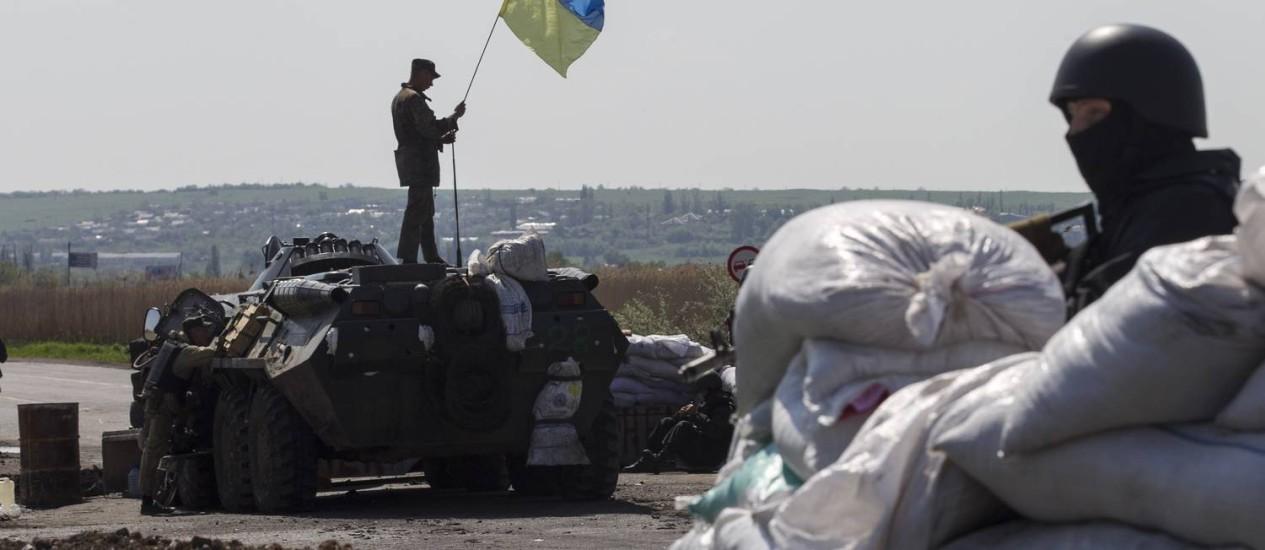 Soldado levanta bandeira da Ucrânia em cima de um veículo blindado em um posto de controle perto da cidade de Slaviansk, no Leste do país Foto: BAZ RATNER / REUTERS