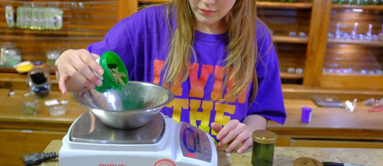Ashley Stanley, empregada da Evergreem Apothecary, em Denver, pesa uma porção de maconha para um cliente, após a legalização da marijuana para uso recreativo no Colorado: negócio está estimulando o mercado imobiliário do estado Foto: Matthew Staver / Bloomberg