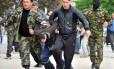 Militantes pró-russos carregam um homem com os olhos cobertos em frente ao prédio do governo regional ocupado por separatistas em Donetsk