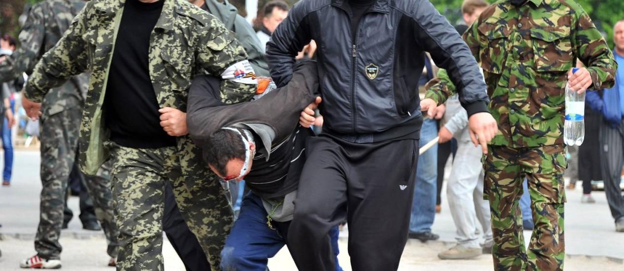 Militantes pró-russos carregam um homem com os olhos cobertos em frente ao prédio do governo regional ocupado por separatistas em Donetsk Foto: GENYA SAVILOV / AFP